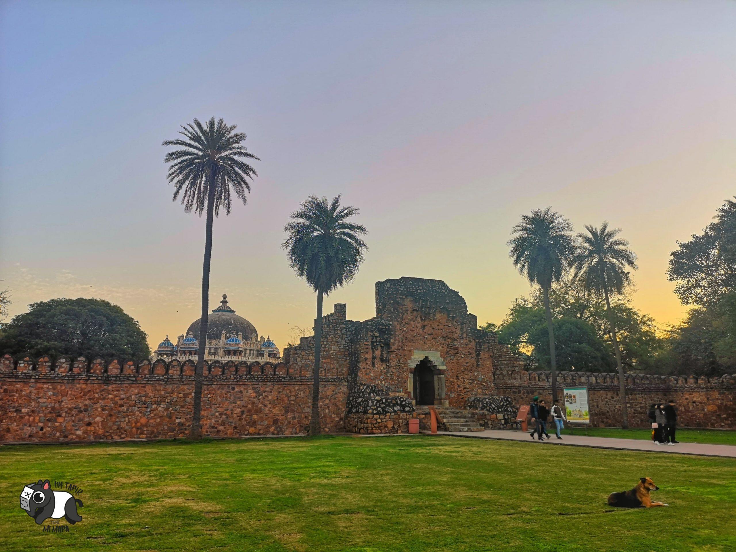 Entrada a Isa Khan Tomb con perro descansando en el jardín.